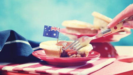 Photo for Traditional Australian Meat Pies for Australia or Anzac Day holiday party food, in red, white and blue table setting, with applied vintage wash filter. - Royalty Free Image