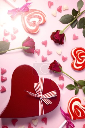 Photo for Happy Valentines Day pink background with scattered lollipops, roses and heart shaped gift over head with lens flare. - Royalty Free Image
