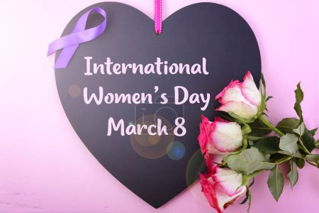 Photo for International Womens Day, March 8, heart shaped blackboard greeting with purple ribbon symbol and pink roses on pink wood background with lens flare. - Royalty Free Image