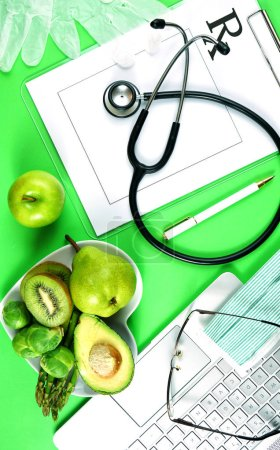 Photo for Prescription for good health overhead stop motion with doctors desk, rx form, stethoscope, healthy fresh food on symbolic green background. - Royalty Free Image