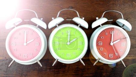 Photo pour Retourner les horloges une heure pour l'automne Décalage horaire sur fond de bois sombre avec une fusée éclairante . - image libre de droit
