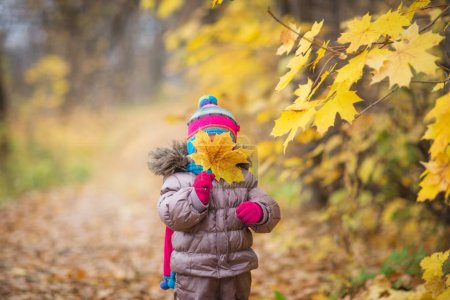 Photo for Happy little child, baby girl laughing and playing leaves in the autumn on the nature walk outdoors. - Royalty Free Image