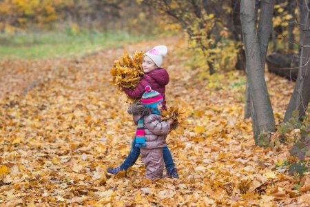 Photo for Happy children. girl holding bunch of autumn yellow leaves on the nature walk outdoors. - Royalty Free Image