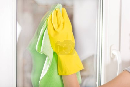 Woman hand with yellow protective glove and green rag cleaning window at home. Selective focus, close up