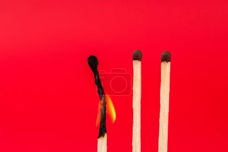 Photo for Three matches and one burned on red background - Royalty Free Image