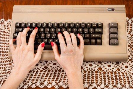 Photo pour Femme tapant sur un vieux clavier d'ordinateur - image libre de droit