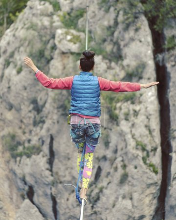 Photo for Highliner on a rope. Highline on a background of mountains. Extreme sport on the nature. Balancing on the sling. Equilibrium at altitude. - Royalty Free Image