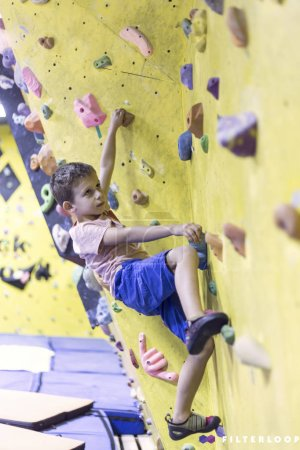 Photo pour Enfant grimpeur gratuit jeune garçon pratiquant sur des rochers artificiels dans la salle de gym, bloc - image libre de droit