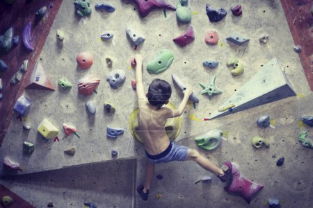 Photo for Little boy climbing a rock wall indoor. - Royalty Free Image