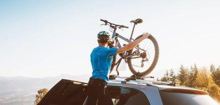 Mountain biker man take of his bike from the car r...