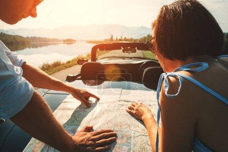 Photo pour Couple plans de voyageurs en voiture itinéraire avec la carte - image libre de droit