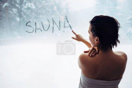 """Photo pour Femme a écrit """"sauna"""" mot sur fenêtre brouillée dans la zone de soudage - image libre de droit"""