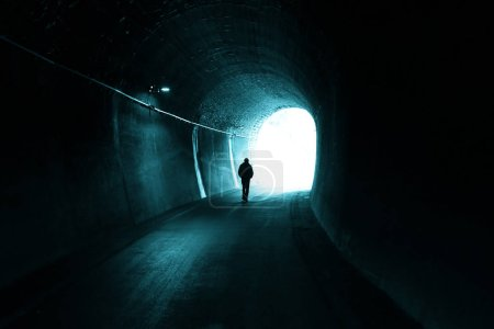 Photo for Man walks alone in dark tunnel with light in the end - Royalty Free Image