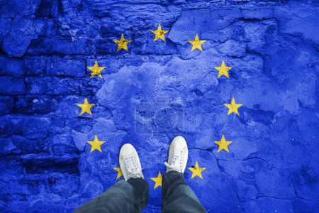 Photo for Top view of a man standing on damaged aged city floor with painted European Union flag. Point of view perspective used. Conceptual EU disintegration background. - Royalty Free Image