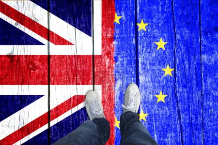 Point of view of a man standing on aged wooden boards painted with United Kingdom and European union flags.