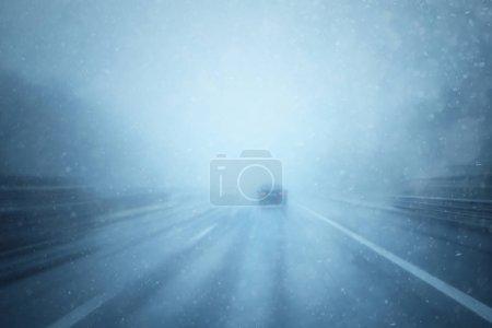 Photo pour Mauvaises conditions météorologiques sur l'autoroute avec conduite automobile. Fortes chutes de neige et de pluie. Motion blur visualise la vitesse et la dynamique. Perspective personnelle utilisée . - image libre de droit