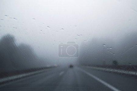 Photo pour Autoroute floue abstraite conduisant un jour de pluie. Mauvaises conditions météorologiques sur la route. Effet flou visualise mauvaise vision et la dynamique. Concentration sélective utilisée . - image libre de droit