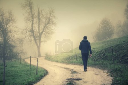 Photo for Back view of a man walks alone on misty countryside road with electric fence. - Royalty Free Image