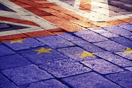 Conceptual sunny United Kingdom and European Union flag on street floor.