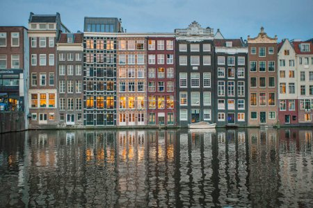 Holland, Netherlands - 10 May, 2018: Amsterdam canal Singel with typical dutch houses illuminated in the evening. Illuminated buildings reflection in the Amsterdam canal.