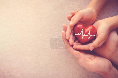 Photo pour Adulte et enfant mains tenant un coeur rouge avec cardiogramme, santé amour et notion de famille - image libre de droit