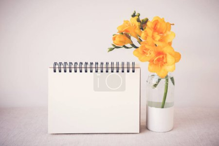 Notepad with yellow flowers in vase mock up,  toning
