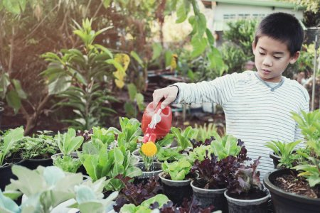 young asian boy watering plants in reuse old plastic containers