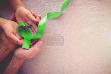 Photo pour Adulte et enfant mains tenant Greenribbon de chaux, de sensibilisation à la santé mentale et de sensibilisation du lymphome - image libre de droit