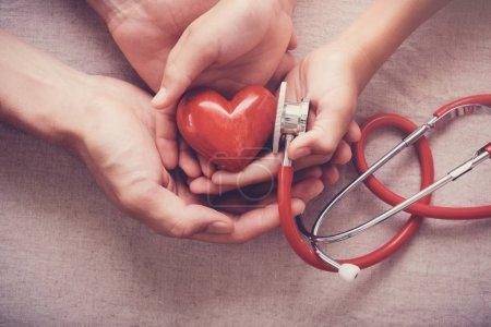 Photo pour Enfant et adulte tenant un coeur rouge avec stéthoscope, santé cardiaque, notion d'assurance maladie - image libre de droit