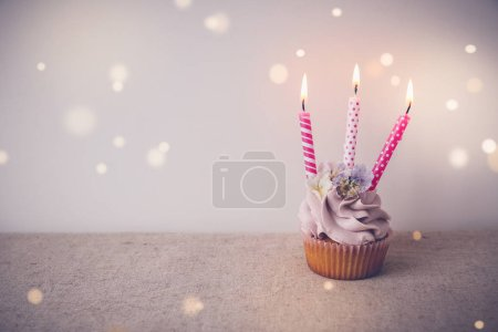 Pink and purple Birthday cupcake with three candles, fairy light bokeh copy space toning background