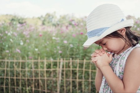 Asian girl child praying with eyes closed, christianity faith concept