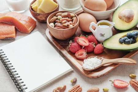 Background with different food and notebook, ketogenic diet, low carbs, high good fat.