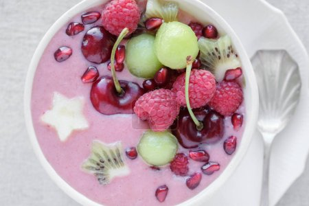 Photo for Red pink and green smoothie bowl with cherry, melon, strawberry, raspberries and pomegranate , christmas fun food - Royalty Free Image