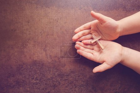 Wooden cross on praying child hands, copy space dark toning background