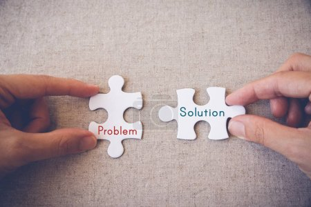 Hands with puzzle pieces and problem solution words