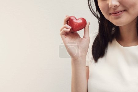 Asian young woman holding red heart, health insurance and donation concept