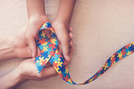 Photo for Hands holding puzzle ribbon for autism awareness - Royalty Free Image