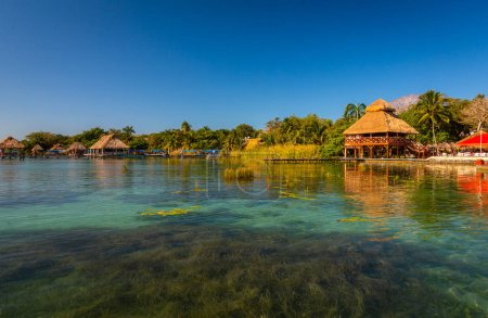 Photo for Laguna de Bacalar is also known as the Lagoon of Seven Colors, in Bacalar, Mexico. The crystal clear waters and white sandy bottom of the lake cause the water color to morph into varying shades of turquoise, blue, and deep indigo throughout the day a - Royalty Free Image