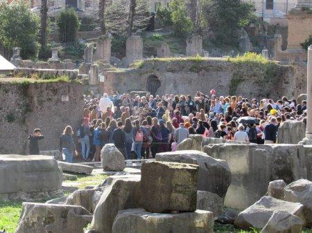 Photo pour Une reconstitution annuelle de la procession funèbre de Jules César devant le temple de Divus Iulius dans le Forum romain avec de nombreux touristes et habitants regardant l'événement - image libre de droit