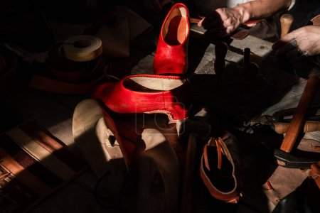 Shoe master sews shoes and leather.