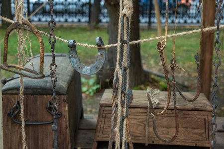 Hooks, horseshoes, chains hanging on the rope.