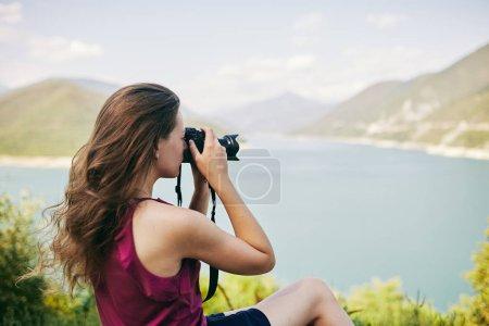 Photo pour Jeune fille touristique prenant des photos de montagnes et le lac. La Géorgie. L'été. Août. Fille faisant une séance photo de montagne . - image libre de droit