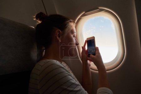 Photo pour Une jeune fille regarde par la fenêtre de l'avion. Le passager regarde par la fenêtre de l'avion. La fille prend des photos avec son téléphone de la vue de la fenêtre - image libre de droit