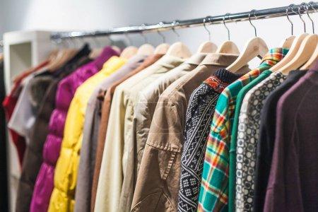 Photo pour Sélection colorée de vêtements pour hommes et femmes accrochés à des cintres dans un centre commercial pour un concept de vente de magasin - image libre de droit