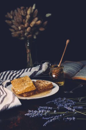 selective focus of honeycombs on plate, lavender and jar with honey stick on black background
