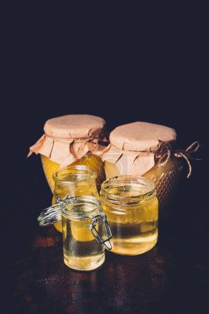 selective focus of different jars with honey on black background