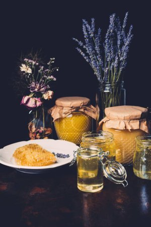 selective focus of jars with honey, dried flowers, lavender and honeycomb on black background