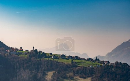 small village on a hill, blue sky with mountains