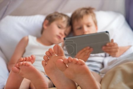 Two boys holding smartphone, tablet sitting on chair, focus on childrens feet.