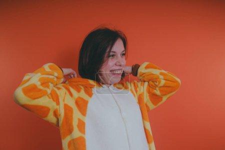 Photo pour Pyjama en forme de girafe. portrait émotionnel d'une fille sur fond orange. fille folle et drôle dans un costume. animateur pour les fêtes d'enfants - image libre de droit